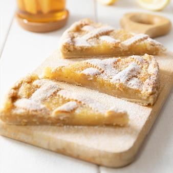 Drie stukken van zelfgemaakte zandkoek citroentaart bestrooid met poedersuiker op een snijplank.