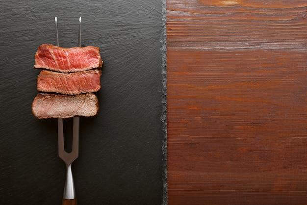 Drie stukken vlees op een vork voor vlees. drie soorten vlees braden, zeldzaam, medium, goed gedaan.