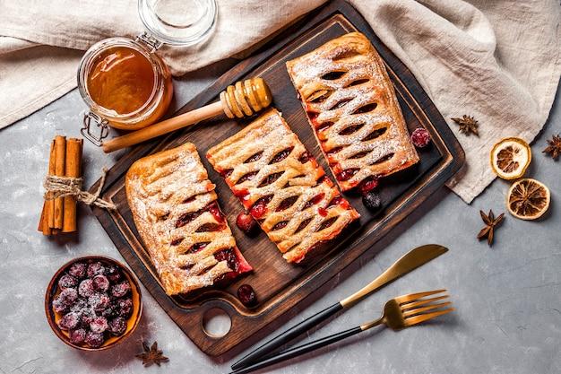 Drie stuks zoete taart met bessen en poedersuiker