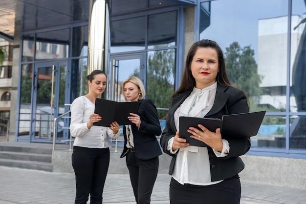 Drie succesvolle bedrijfsdames die zich voor centrale ingang van bureau bevinden