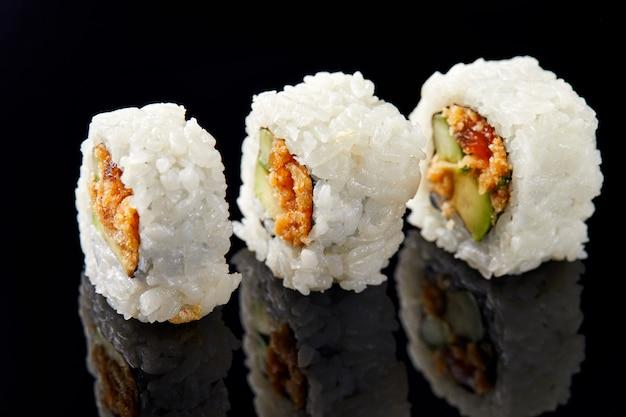 Drie sushi op een rij op zwart met reflectie