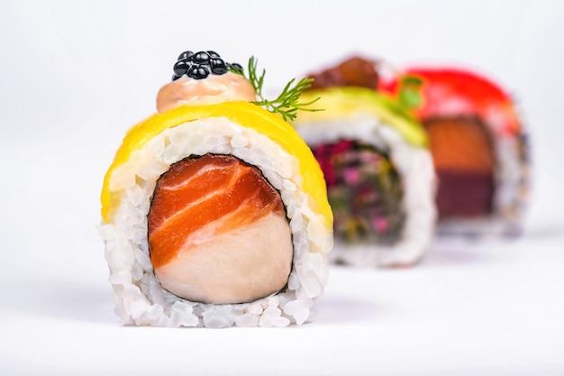 Drie sushi rolt met zalm, avocado, tonijn en komkommer op wit wordt geïsoleerd