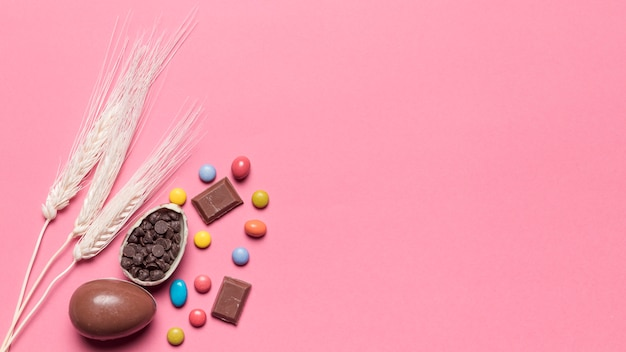 Drie tarweoren met chocoladepaaseieren en gemsuikergoed op roze achtergrond