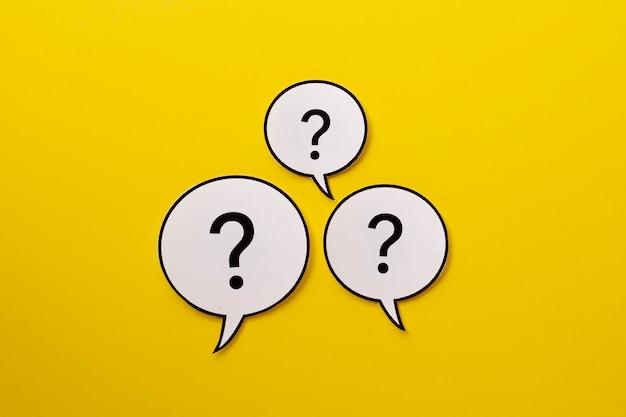 Drie tekstballonnen met vraagtekens hebben een felgele achtergrond