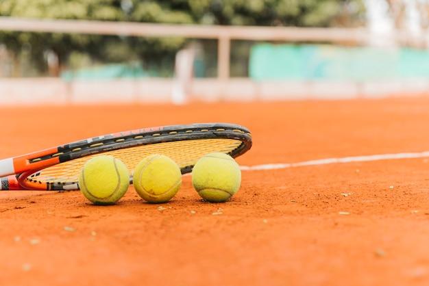 Drie tennisballen met racket