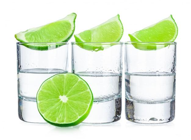 Drie tequilaschoten met kalk die op wit wordt geïsoleerd