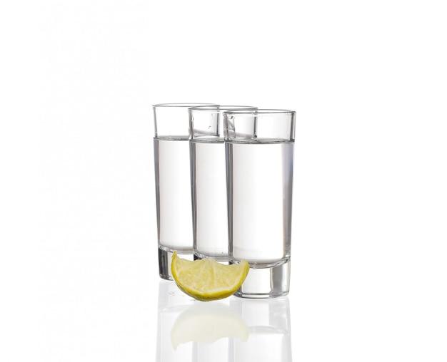 Drie tequilaschoten met kalk die op witte achtergrond wordt geïsoleerd