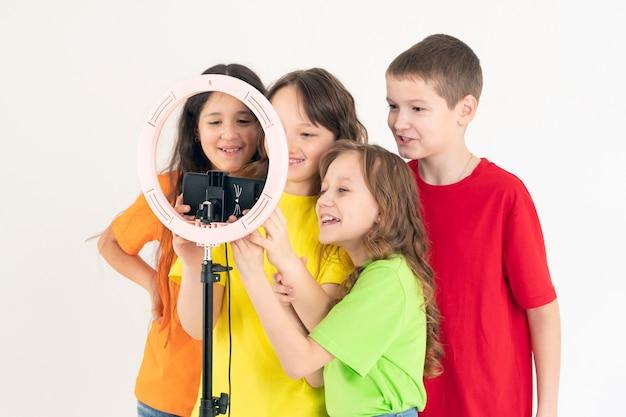 Drie tienermeisjes en een jongen die glimlachen en een video schieten