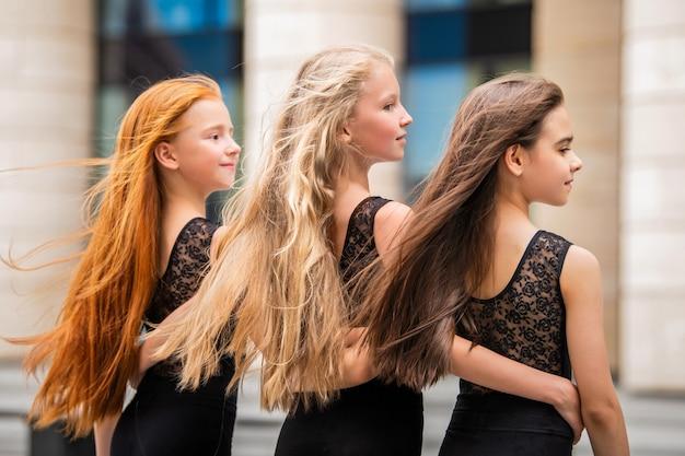 Drie tienermeisjes met losse haren blonde roodharige en brunette, staan in profiel buiten in de zomer. vloses ontwikkelen zich in de wind.