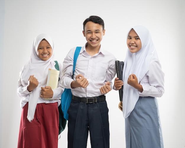 Drie tieners in schooluniformen glimlachten met een opgewonden handgebaar bij het dragen van een rugzak en een ...