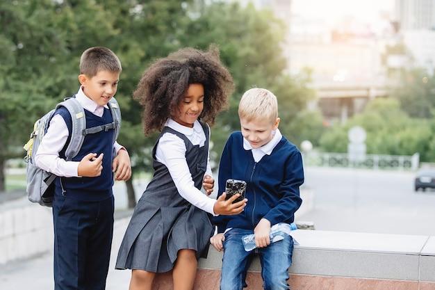 Drie tieners in schooluniformen kijken naar een smartphone. afrikaans, blond en jongen