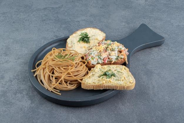 Drie toastbrood met salade en spaghetti op zwart bord