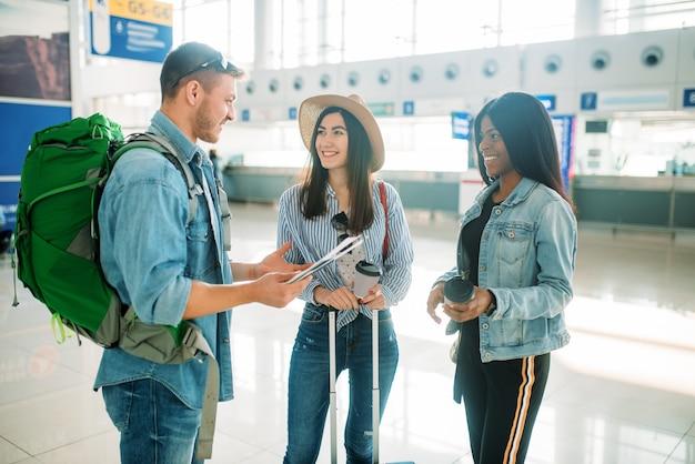 Drie toeristen met bagage die op vertrek in luchthaven wachten. passagiers met bagage in de luchtterminal
