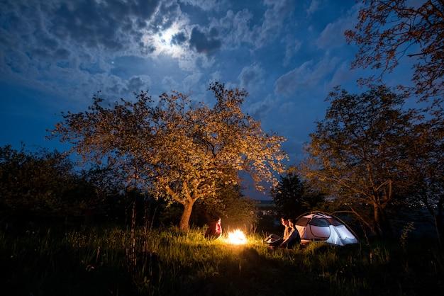 Drie toeristen zitten bij een kampvuur in de buurt van tent onder bomen en nachtelijke hemel met de maan. nacht kamperen