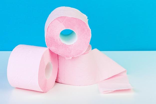 Drie toiletpapierbroodjes die op witte lijst met blauw worden geïsoleerd