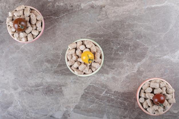 Drie tomaten op de broodkruimels in de kom naast de aar, op het marmeren oppervlak