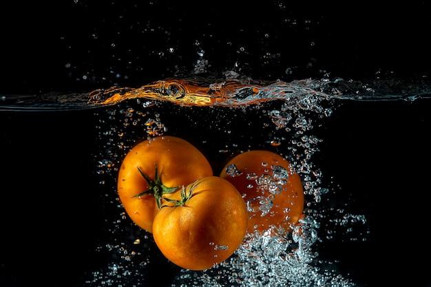 Drie tomaten spatten op water