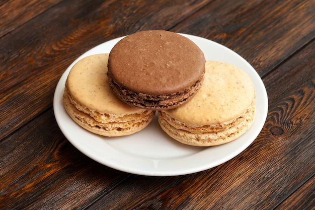 Drie traditionele franse chocolade macarons op plaat
