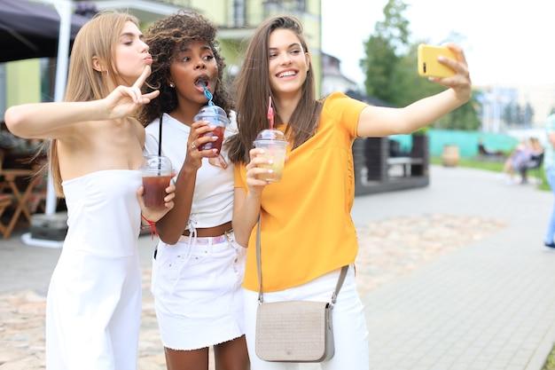 Drie trendy coole hipstermeisjes, vrienden drinken een cocktail en nemen selfie op de achtergrond van de stad.