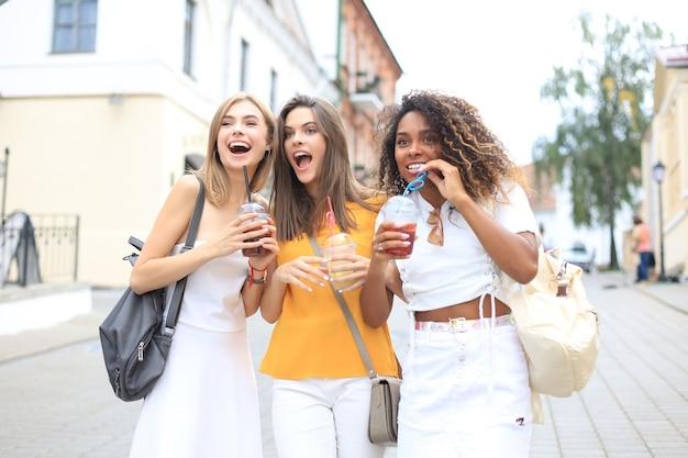 Drie trendy coole hipstermeisjes, vrienden drinken een cocktail op de achtergrond van de stedelijke stad.