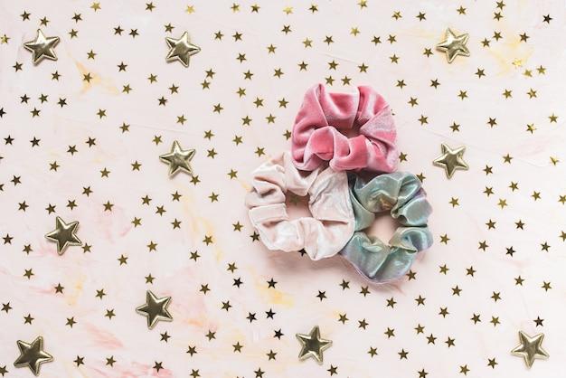 Drie trendy fluweelroze en holografische glanzende metallic scrunchies en gouden sterrenconfettien op roze achtergrond.
