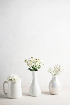 Drie vazen met bloemen op tafel