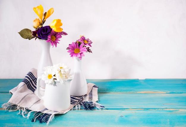 Drie vazen met heldere bloemen op tafel