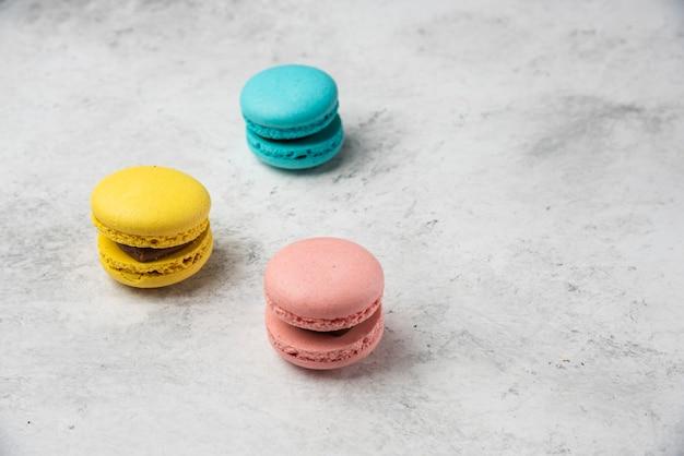 Drie veelkleurige macarons dessert op witte achtergrond.