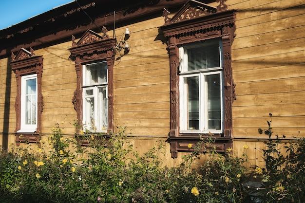 Drie vensters in rij op de muur van een oud traditioneel russisch houten huis versierd met houtsnijwerk