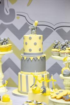 Drie verdiepingen tellende taart en cupcakes versierd met olifanten op tafel tijdens een verjaardagsfeestje