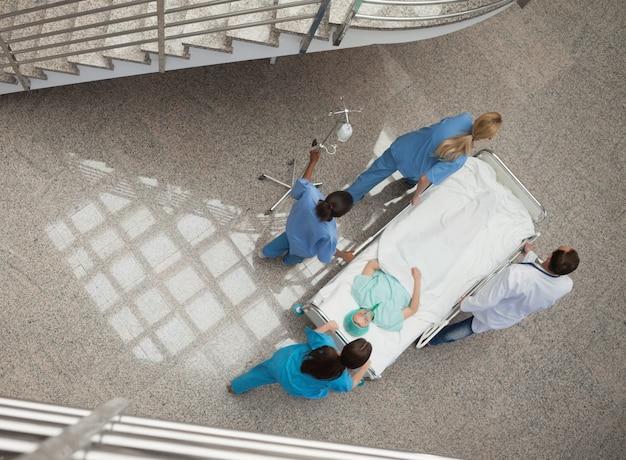 Drie verpleegsters en één arts die een patiënt in een brancard duwen