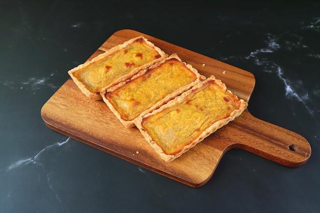 Drie verrukkelijke pompoentaartjes op houten broodplank geïsoleerd op zwarte keukentafel