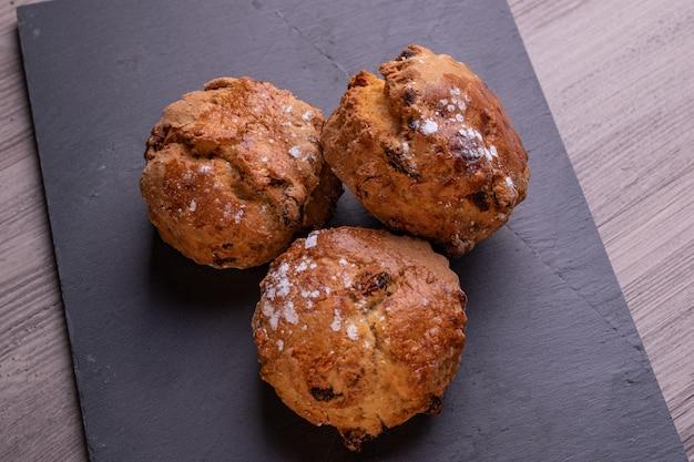 Drie vers gebakken fruit scones op leisteen plaat. rustiek oppervlak.