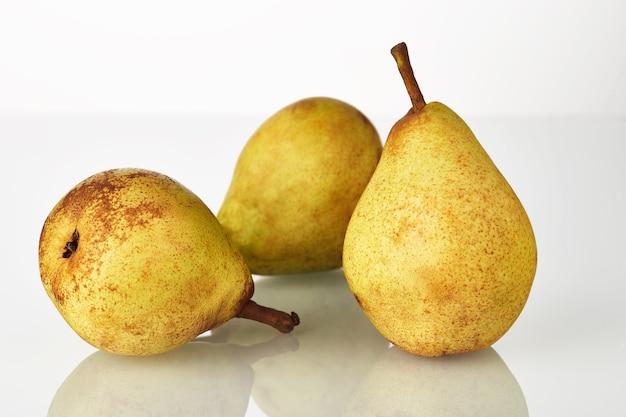 Drie vers sappig geelgroen perenfruit dat op de witte achtergrond wordt geïsoleerd.