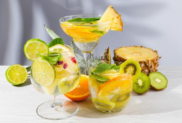 Drie verschillende cocktails met fruit op een lichte houten tafel.