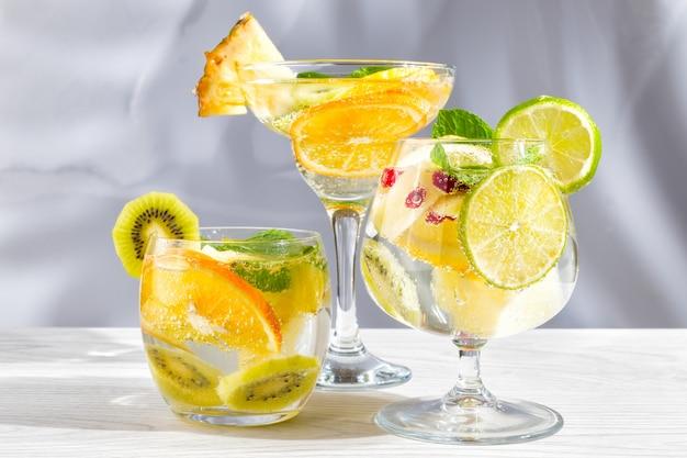 Drie verschillende glazen met cocktails met fruit en bessen