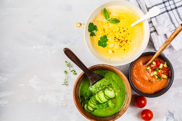 Drie verschillende groentesroomsoepen in kommen op grijze maïs, komkommer en gazpacho-soepen,