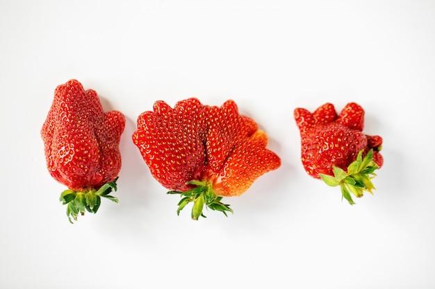 Drie verschillende ongebruikelijk gevormde aardbeien op de witte achtergrond