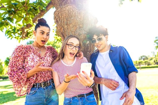 Drie verschillende studenten die verbaasde gezichten maken die mond en ogen verspreiden, wijzend en kijkend naar een smartphone die tijd doorbrengt in de natuur van het stadspark. kracht van nieuwe wifi-technologie die mensen van alle leeftijden verslavend maakt