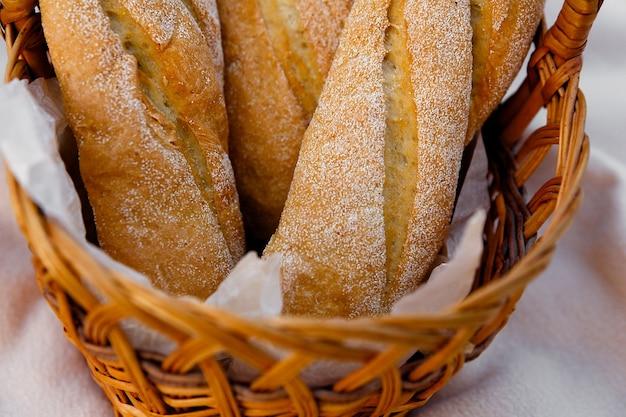Drie verse baguettes liggen in een rieten mand