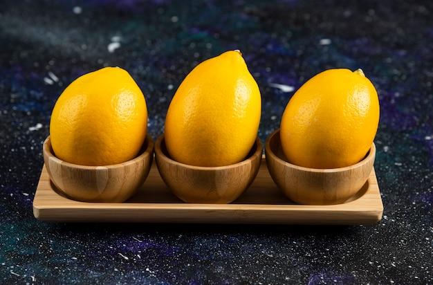 Drie verse citroenen op een houten bord over zwarte ondergrond.