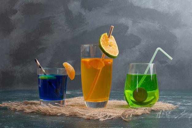 Drie verse drankjes op marmeren tafel.