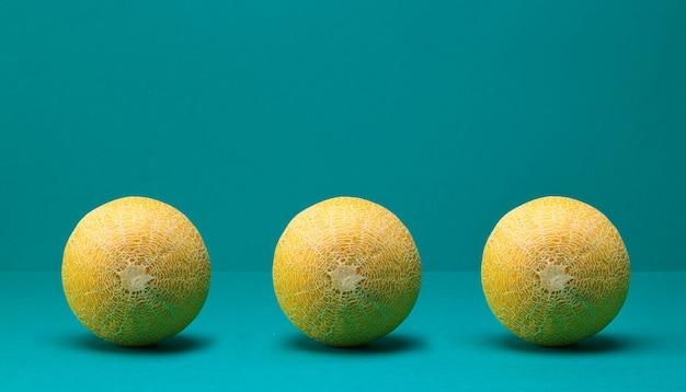 Drie verse hele rijpe meloenen op turquoise kleur achtergrond