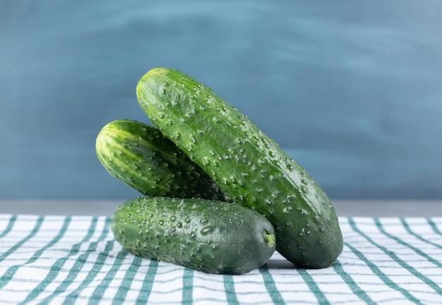 Drie verse komkommers geïsoleerd op een tafellaken. hoge kwaliteit foto