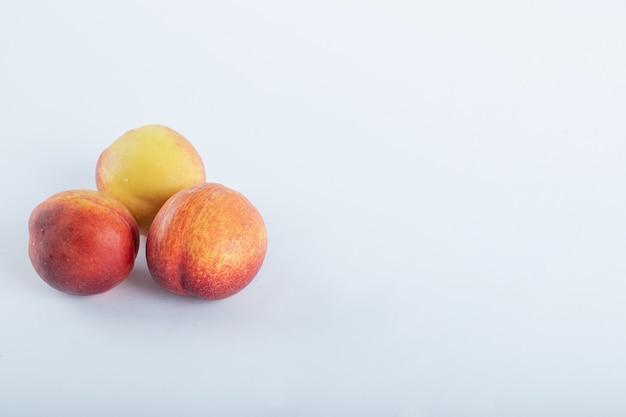 Drie verse nectarines op wit.