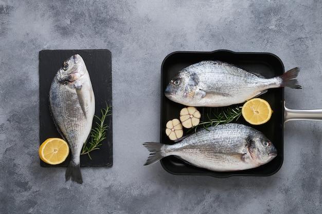 Drie verse rauwe zeebrasemvissen (dorado) op grijze tafel. gezond voedselconcept. bovenaanzicht, kopiëren
