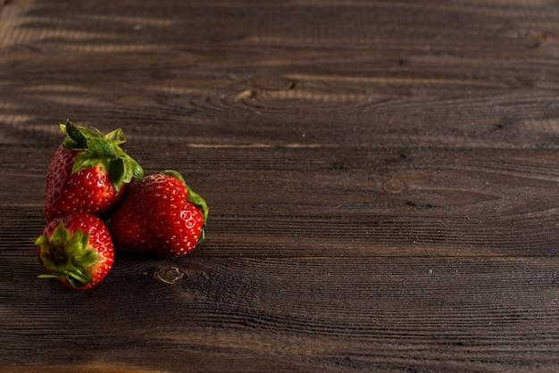 Drie verse, sappige aardbeien liggen op een oude tafel van een donkere houten achtergrond.