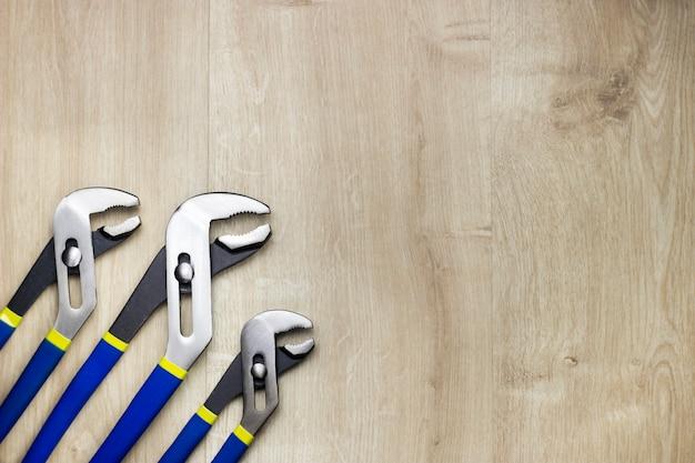 Drie verstelbare tangen op hout achtergrond. verstelbare sleutels.