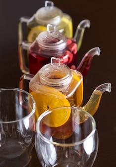 Drie vierkante theepotten met verschillende fruitsmaken van thee