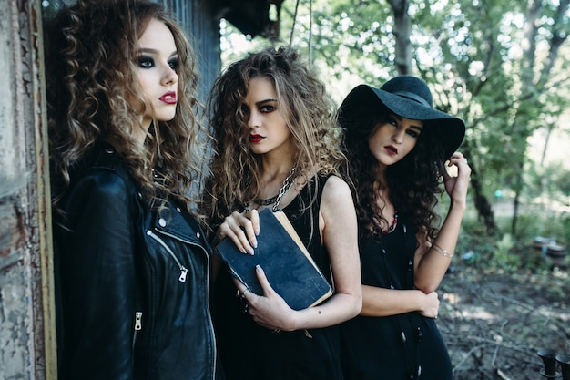 Drie vintage vrouwen als heksen poseren bij een verlaten gebouw aan de vooravond van halloween